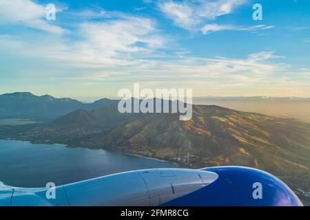 View of the tropical island of O'ahu from above over wing during golden hour
