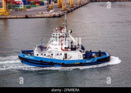 Barcelona, Spain - September 26, 2015: Tugboat Montbrio moving in international port of Barcelona, built in 2007, with 29.5 m Length and 77 Tn pull Bo