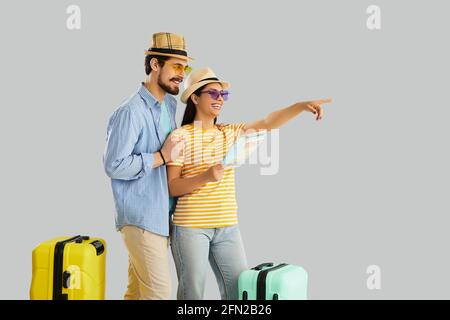 Happy couple traveler with map planning honeymoon vacation trip studio shot Stock Photo