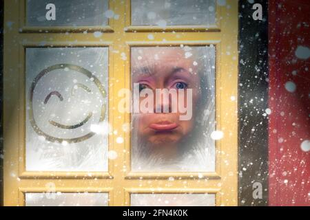 Sad woman stuck indoors by a window during a winter snow storm with happy expression squiggled on the glass. Trapped in boredom