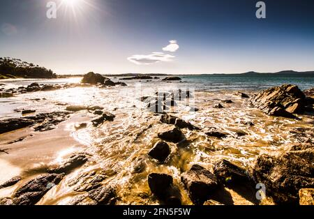 Tranquility meets turbulent seas at high tide with waves swamping marine rocks. Swansea Tasmania Australia