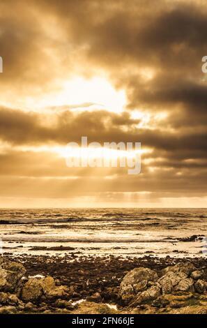 Majestic ocean landscape with afternoon sunlight piercing atmospheric rain clouds. Granville Harbour, West Coast Tasmania, Australia
