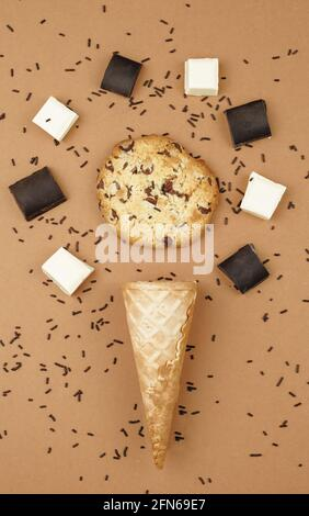 Overhead shot of an ice cream cone with a chookie surrounded by pieces of chocolate, on a brown background. Ingredients of a chocolate ice cream. Ice