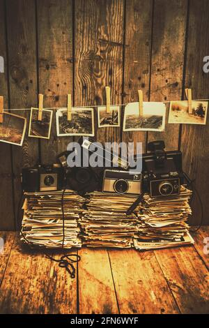 Classic still-life photography on a stack of old cameras from 1950 to 1980 on a pile of vintage photographs