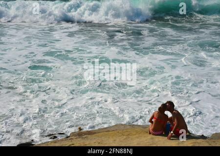 Seascape with a young couple sitting on a rock off the shore of Oceanside Beach in San Diego, California USA.
