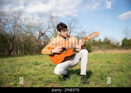 Young musician, kneeling plays the classical guitar in a field in the open air