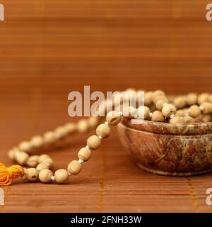 Buddhist prayer beads in a bowl on wooden background. Mindfulness or meditation concept. close up, copy space.