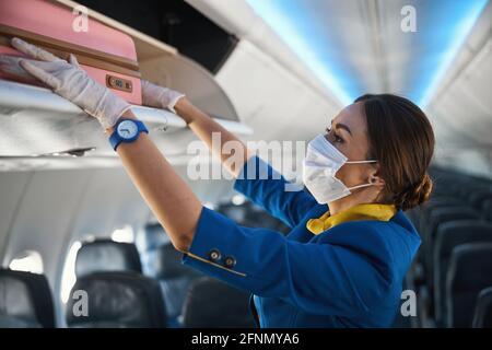 Cabin crew member shoving suitcase to overhead bin