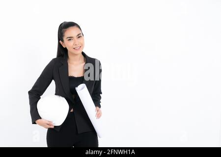 Portrait young engineer woman wearing black suit holding blueprint and white safety-helmet in shot studio isolated on white background.