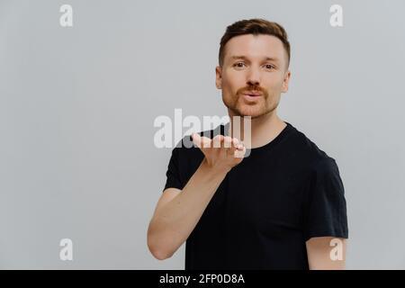 Young handsome guy sending air kiss at camera