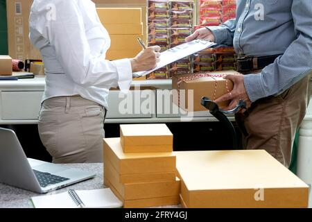 Small business woman Worker delivery service and working packing box, business owner working checking order to confirm before sending customer in post