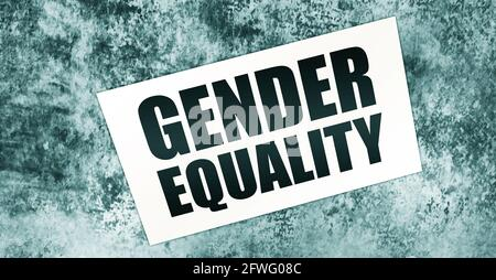 Gender Equality words on card on wooden table. Equal rights social concept.