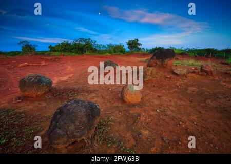 Evening light with moon, red desert soil, and large boulders in Sarigua national park, Herrera province, Republic of Panama, Central America.
