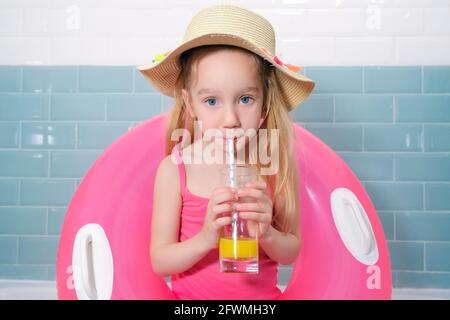 Funny sad little girl with a pink rubber ring, wearing a hat and having a cocktail in the bathroom. Quarantine vacation concept