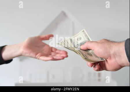 Two people (male and female) passing money against a white house. Mortgage, housing market, home loans and property, management concept. No people. Co