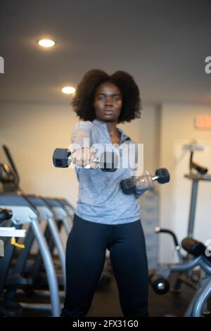Woman working out with dumbbells at home gym. close up, one person, fitness model, African American, African model, sportswear, natural hair model