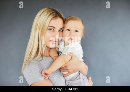 Smiling beautiful woman holding her eleven month old baby with gray background. Maternity concept