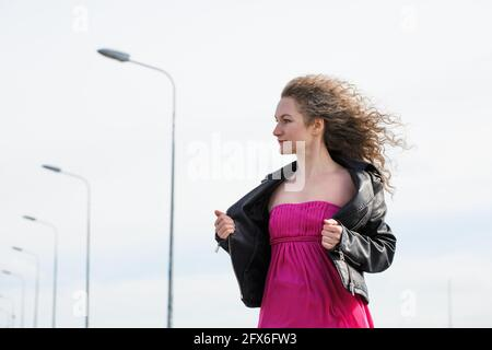 caucasian curly-haired woman in a black leather jacket and a pink dress against the background of a cloudy sky and pillars with lanterns