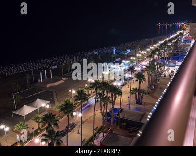 Top aerial view overlooking night lit Finikoudes Palm tree promenade, road with car lights, beach umbrellas near the Mediterranean sea and horizon.