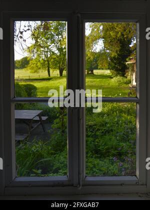 Blick aus dem Fenster in eine gruen, blühende Morgenlandschaft, View out of the window into a green, blooming morning landscape