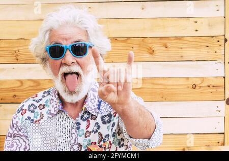 Crazy nice old senior man expression portrait with colorful clotehs - concept of rebel no limit age and youthful people - caucasian elderly male with