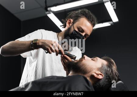 Mustache shaving in barbershop. Barber with dreadlocks in black medical mask trim beard of handsome man at quarantine coronavirus covid-19