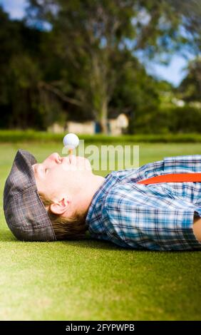 Work Life Balance Sees A Man Take A Break To Lie Down And Relax On A Golf Course With A Tee And Golf Ball In His Mouth Balancing The Act Of Work And P