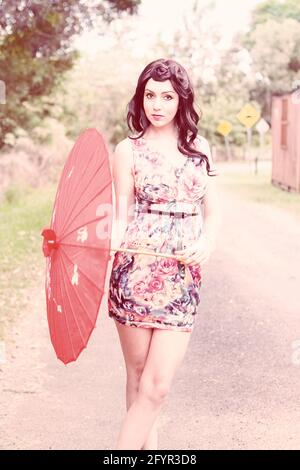 Young Brunette Female Model Woman Poses With A Red Umbrella On A Road Side Location In A 50s Inspired Fashion Portrait