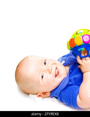 Gurgling Happy Baby With Toy, baby lying on his back witha contented happy expression while playing with a colourful toy, studio close-up on white