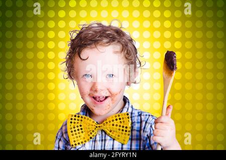 Lovely young child holding chocolate covered cooking spoon when mixing icing for an easter cake, on yellow polka-dot background