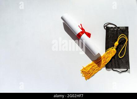 Yellow tassel from graduation cap, paper scroll tied with red ribbon with bow, diploma and black protective face mask on white background, new reality
