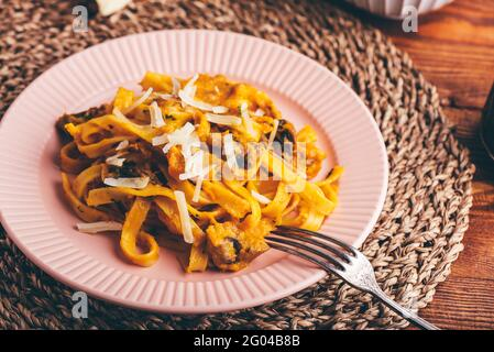 Tagliatelle Pasta with Creamy Pumpkin Sauce and Champignons Garnished with Grated Parmesan Cheese