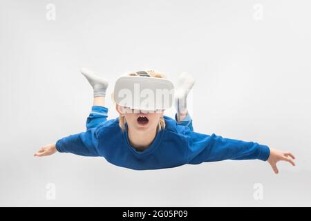 Boy flies in virtual reality glasses. White background. Virtual reality games.