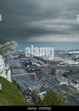 The intricate web of roads of the Wellington Dock port complex, with the famous white chalk cliffs, the English Channel and a dramatic sky behind.