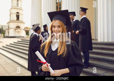 Young smiling girl university graduate in traditional mantle standing and holding diploma in hand