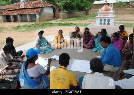 Women attend meeting under the shade of a tree to understand development activities in the field of agriculture, water, health and education in a vill