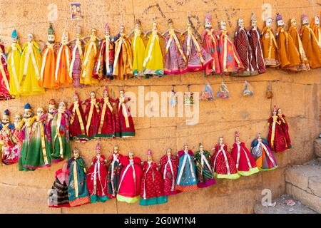 Traditional King and queen, called Raja Rani, handmade puppets or Katputli Sets are hanging from wall inside Jaislamer fort, Rajasthan, India. Dolls i