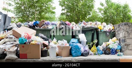 Overloaded dumpster, full garbage container, household garbage bin, trash can, heap of unsorted rubbish: plastic bags, pile of refuse, litter, waste