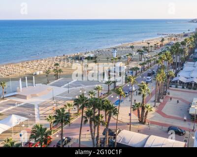 Top aerial view overlooking Finikoudes Palm tree promenade, road with cars, and central beach near the Mediterranean sea in Larnaca city, Cyprus.