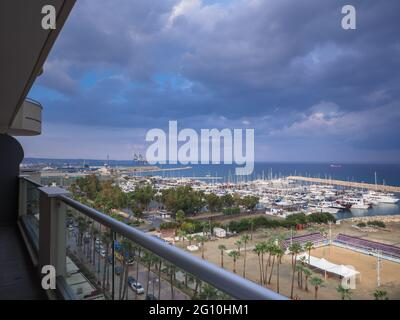 Top aerial view overlooking Finikoudes Palm tree promenade and pier with yachts near the Mediterranean sea in Larnaca town. Industrial cityscape.