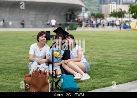 19 5 2021 happy freshly graduated undergraduate and friends in Academic dress gown sit on grass field near West Kowloon Waterfront Promenade, Hong Kon