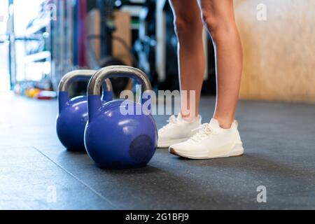 Cropped unrecognizable determined female athlete in sportswear standing resting after during functional training with weights on floor in gym
