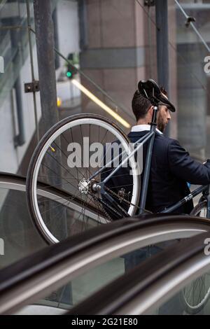 Caucasian businessman carrying bicycle on escalator