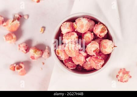 Top view of pink colored strawberry flavored sweet popcorn in white bowl