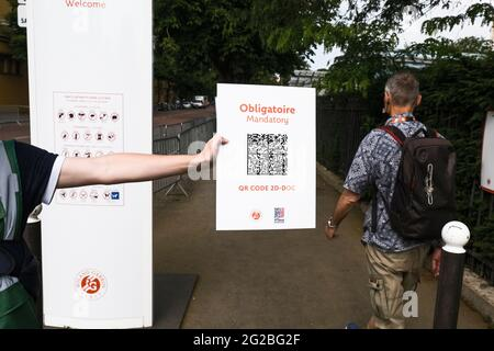Paris, France. 10th June, 2021. Tennis: Grand Slam, French Open. An employee holds a sign at the entrance to remind spectators of a valid Corona test or vaccination. By means of a QR code, access to the tournament site is controlled in this way. Since the new Corona rules on June 9, 2021, more people are allowed back into the Stade Roland Garros. As the curfew in Paris now only starts at 11pm, 5000 spectators will also be allowed onto Centre Court. Credit: Frank Molter/dpa/Alamy Live News