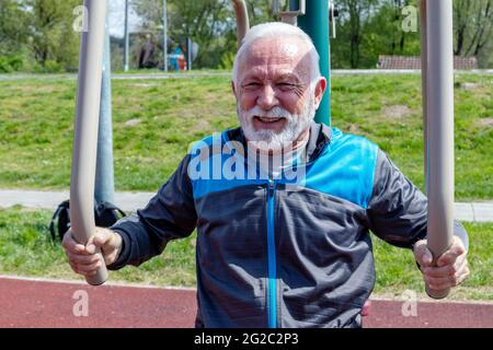 A happy and exhausted senior man exercises on the public gym equipment in the open air.