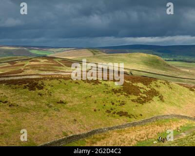 Scenic rural landscape & dark rain clouds (hilly area, rolling sunlit hills, people walking pet dog) - view to Wharfedale, Yorkshire Dales England, UK