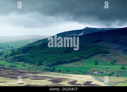 Scenic upland countryside (Wharfedale valley, Simon's Seat peak, high fells, rain falling on hills, dark cloudy sky) - Yorkshire Dales, England, UK.