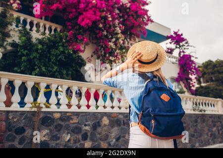 Woman traveler enjoying blooming bougainvillea flowers in Greece. Happy woman walking wearing hat and backpack