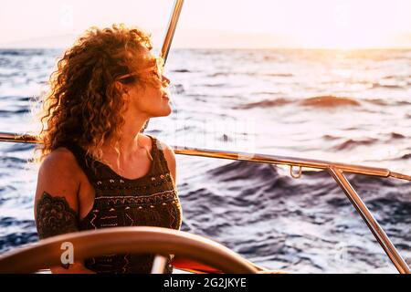 Adult rich woman enjoy luxury lifestyle traveling on sailboat yacht for summer holiday vacation - pretty female people outdoor freedom with ocean sea around in the sunset